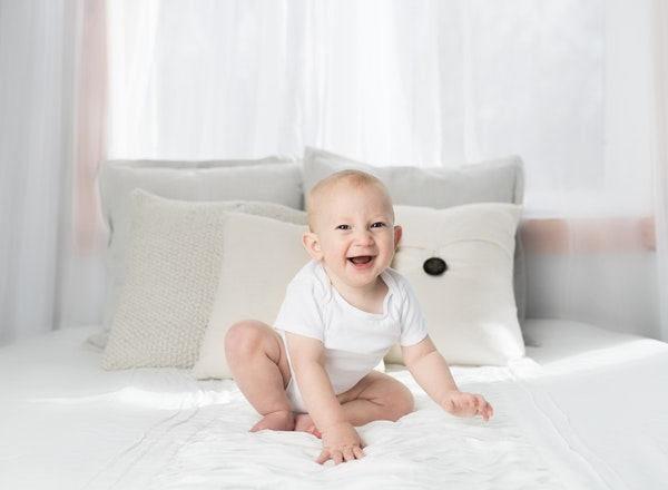 baby in bed laughing